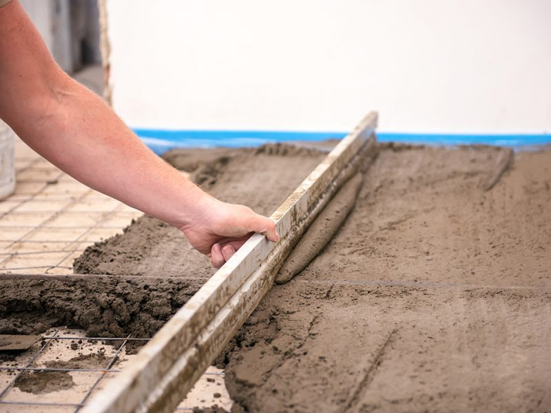 bricklayer aligns cement screed in a newly built house.